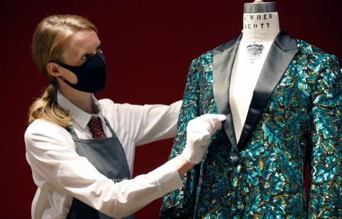 a gallery assistant poses for a photograph next to the oak leaf glamouflage jacket designed for mick jagger by designer lwren scott at christies in london britain june 10 2021  reuters jpg?itok=8nEBqvuR.